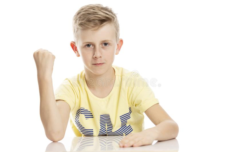 Teen guy shows a fist while sitting at the table. Isolated over white background. Horizontal stock image