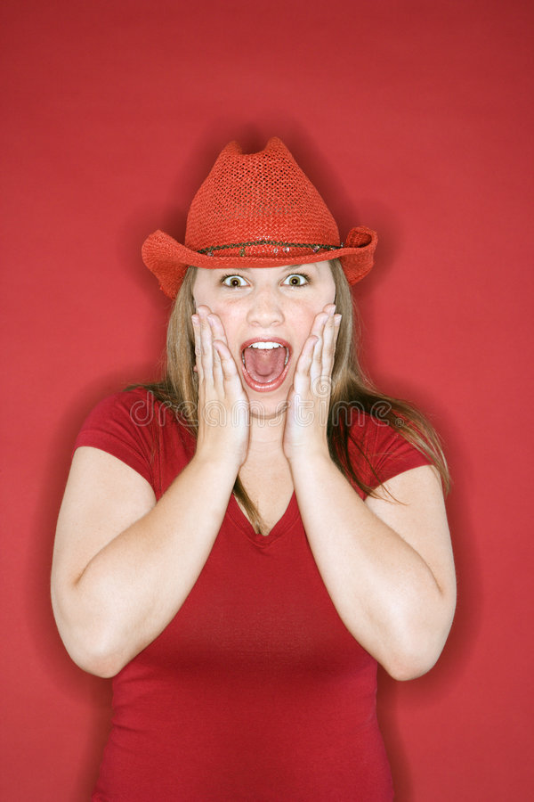Teen with hands on face and mouth open. Young Caucasian female adult in red cowboy hat on red background with hands on face and mouth open stock images