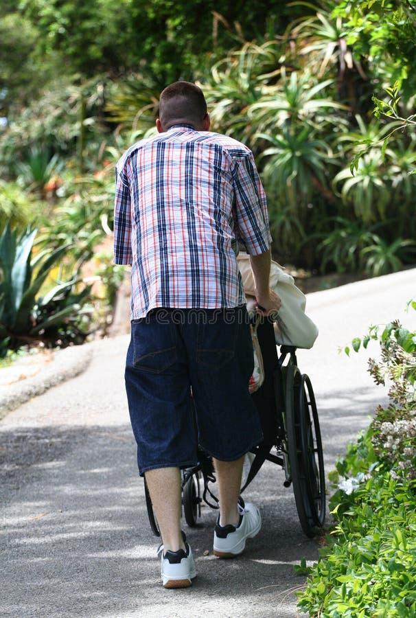 Teen Helping Grandparent. Teenager pushing grandparent in wheelchair stock photos