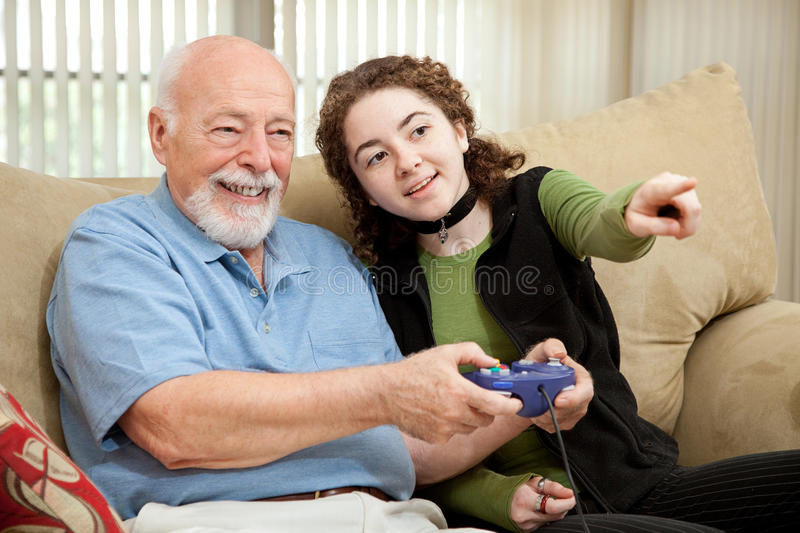 Teen Helps Grandpa with Video Game royalty free stock photos