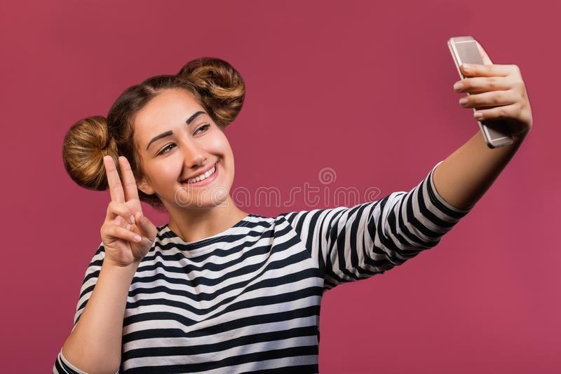 Teen hipster girl with funny hairstyle and face expression making selfie photo on mobile phone, isolated stock photography