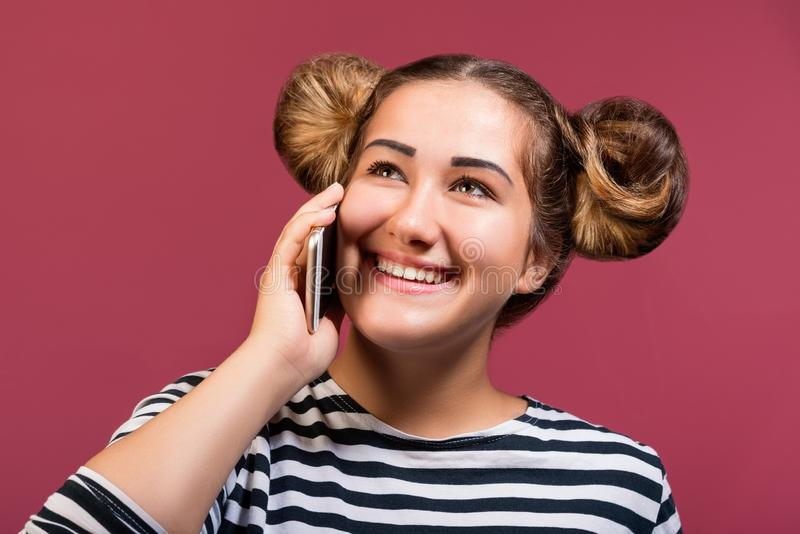 Teen hipster girl with funny hairstyle talking on the phone with smiling face, isolated stock photography