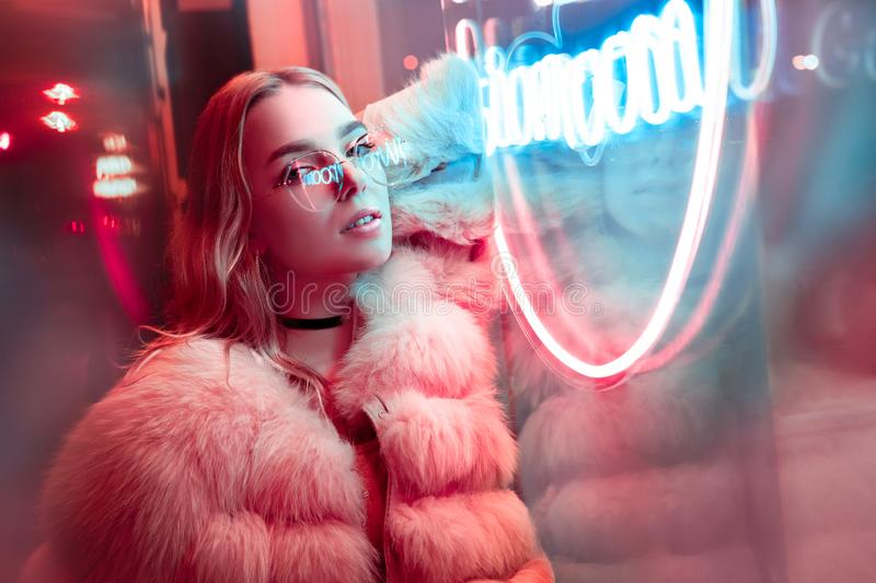 Teen hipster girl posing near neon sign on street, portrait. Teen hipster girl in stylish glasses and fur posing near neon sign on street, female teenager royalty free stock images