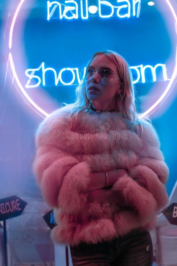 Teen hipster girl in stylish glasses and fur standing near neon sign on street. Teen hipster girl in stylish glasses and fur standing alone near neon sign on stock photography