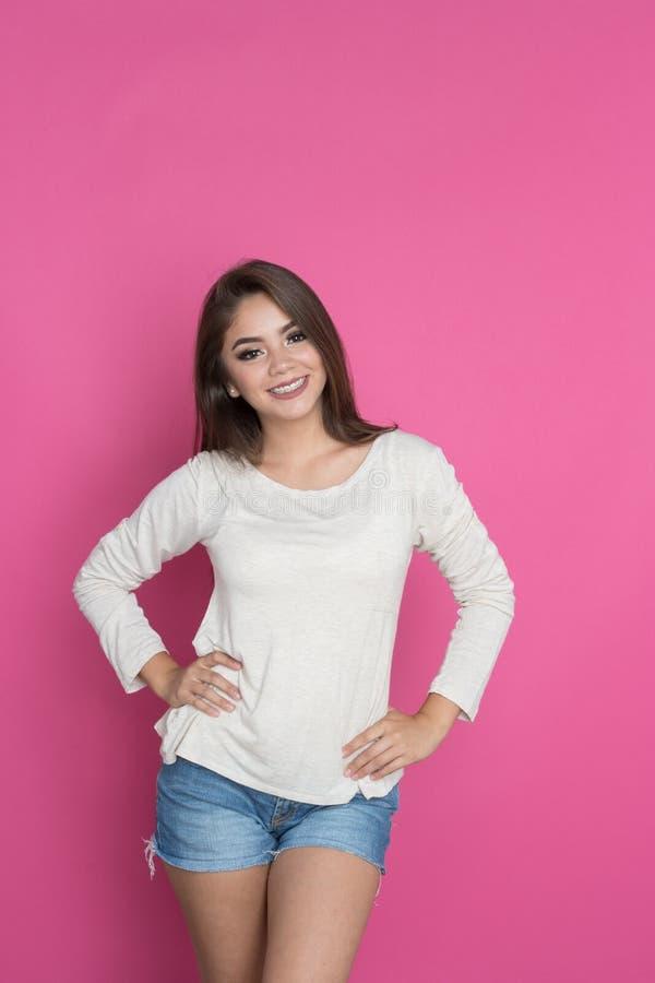 Teen Hispanic Girl On Pink. Teen hispanic girl posing with a pink background stock photos