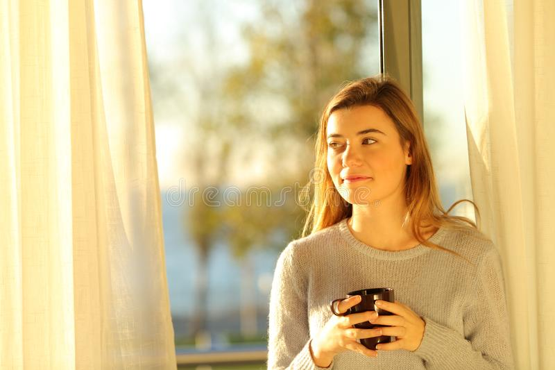 Teen holding a drink thinking at home at sunset stock images