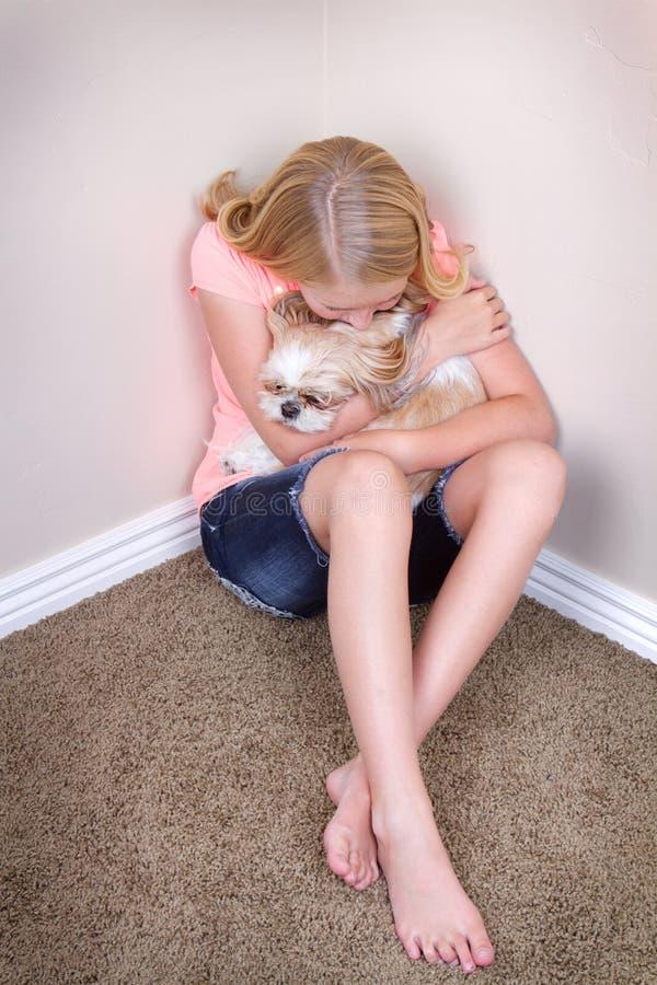 Teen hugging dog in corner royalty free stock images