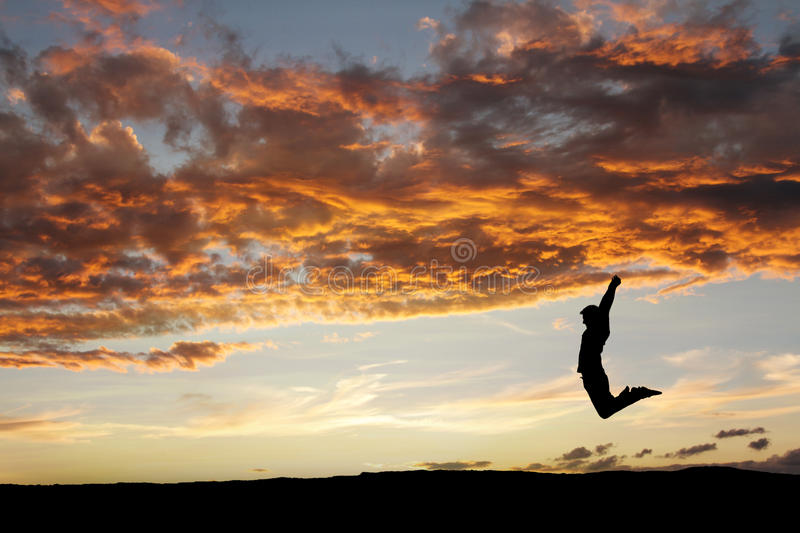Teen jumping in sunset for fun. Silhouette of teen jumping in sunset for fun royalty free stock images