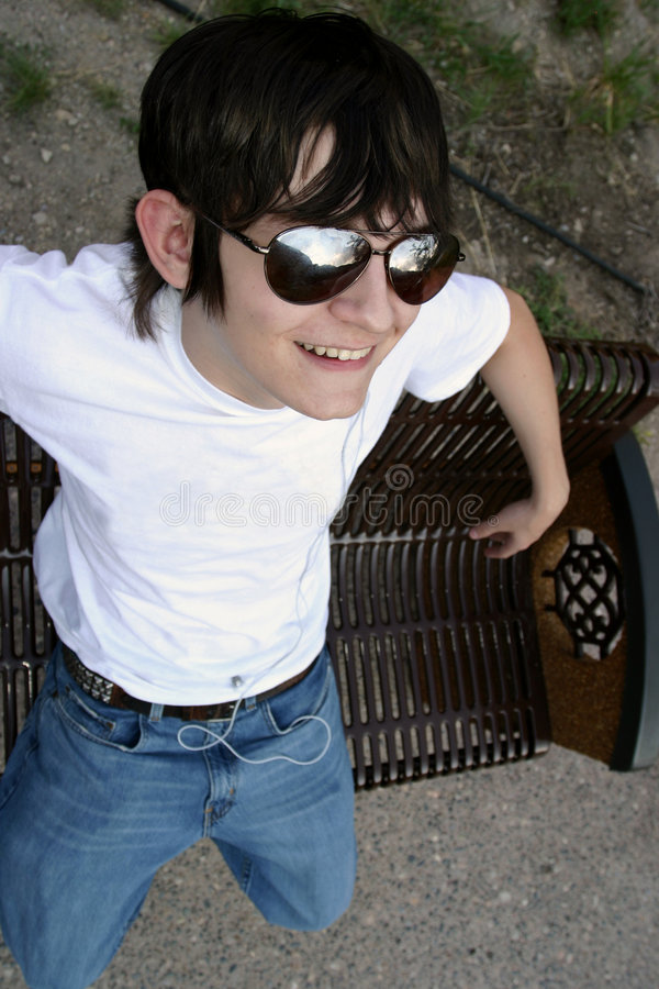 Teen Kicking Back. Cool male teen kicking back on a park bench. He has big sunglasses, a great smile, white t-shirt, blue jeans and an ear bud from an MP3 player stock image