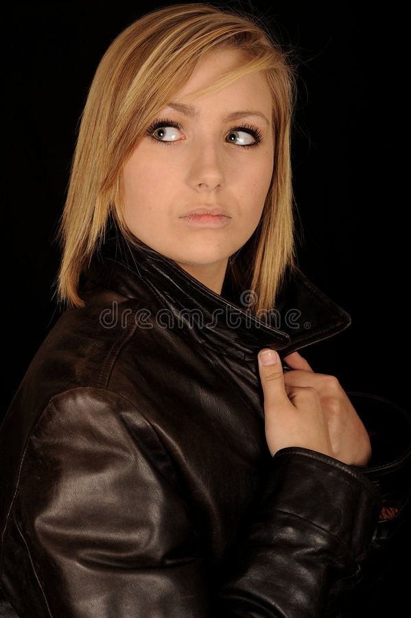 Teen in leather jacket. A portrait of a beautiful teenage girl wearing a black leather jacket royalty free stock image
