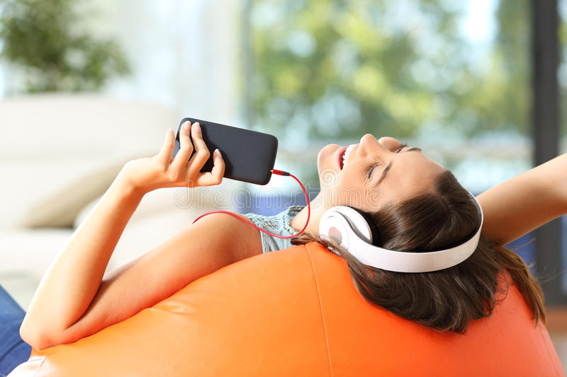 Teen listening music on a pouf stock images
