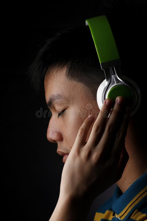 Teen listening to music on a headphone stock photography