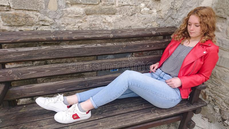Teen in thought. A teen looking down in thought.  thinking girl red jeans young lady bench hair face legs outdoor outdoors female royalty free stock image