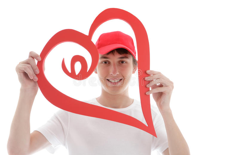 Teen looking through a red love heart. A teenager looking through a red love heart and smiling royalty free stock photography