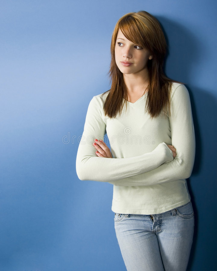 Teen model. Fashionable teenage girl standing against blue wall stock photo