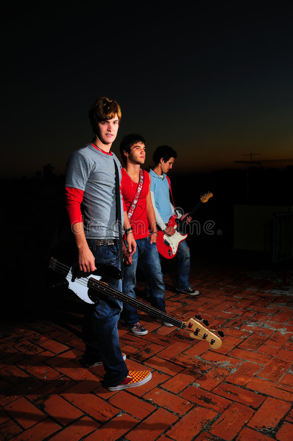 Teen musical band. Portrait of young trendy musiciands holding instruments stock photo