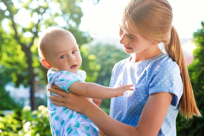 Teen nanny with cute baby outdoors on sunny stock images