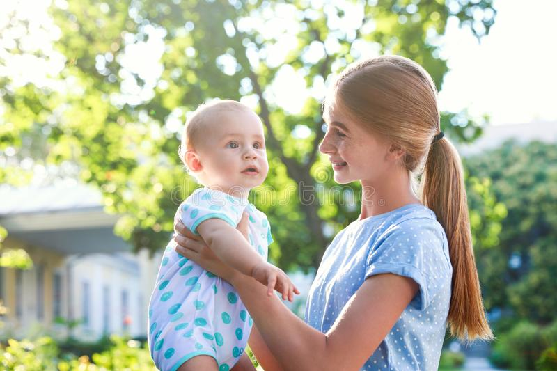 Teen nanny with cute baby outdoors stock photos