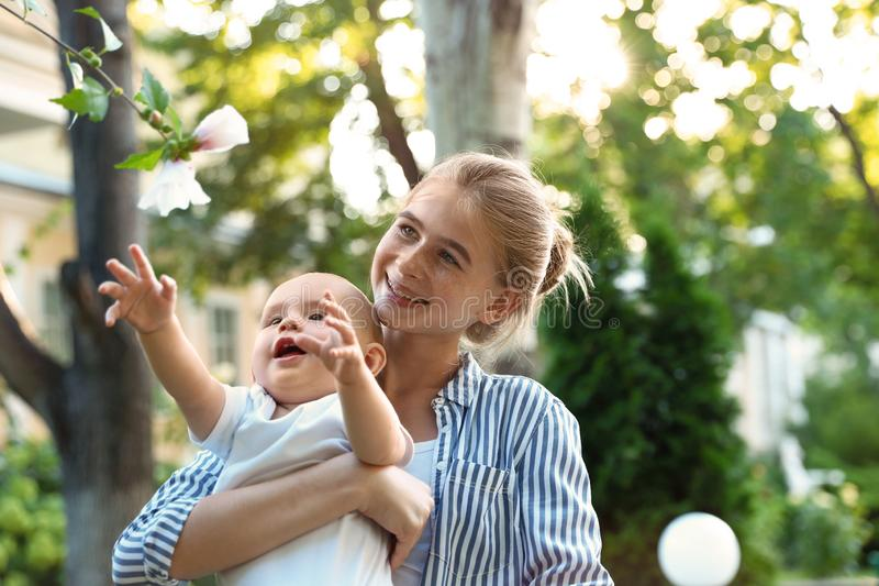 Teen nanny with cute baby in park stock photo