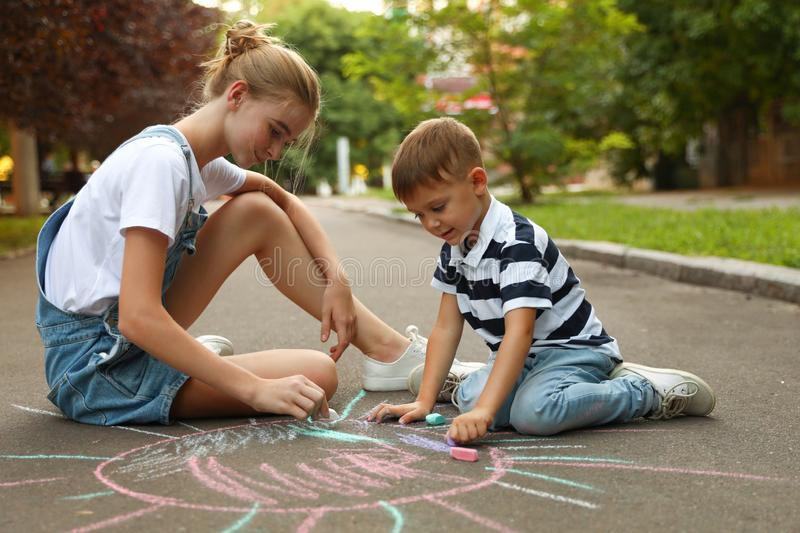 Teen nanny and cute little boy drawing sun with chalks stock photography