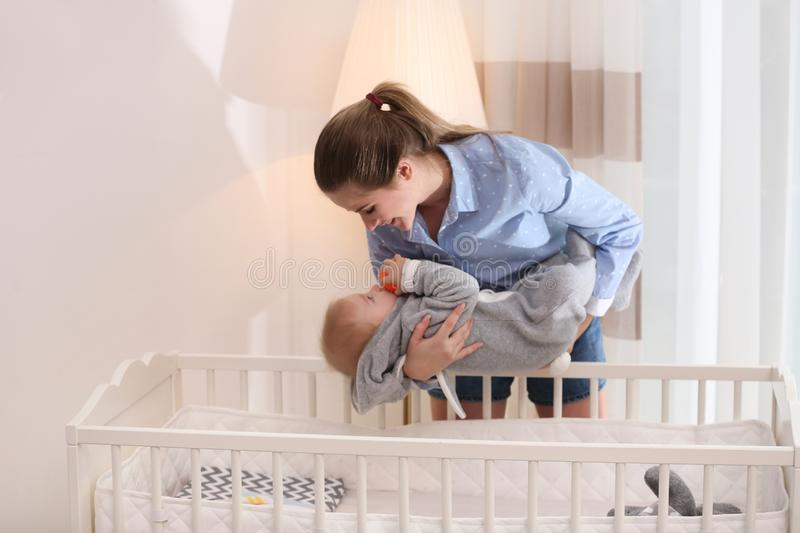Teen nanny putting cute little baby in crib. Daytime sleep. Teen nanny putting cute little baby in crib at home. Daytime sleep stock photography