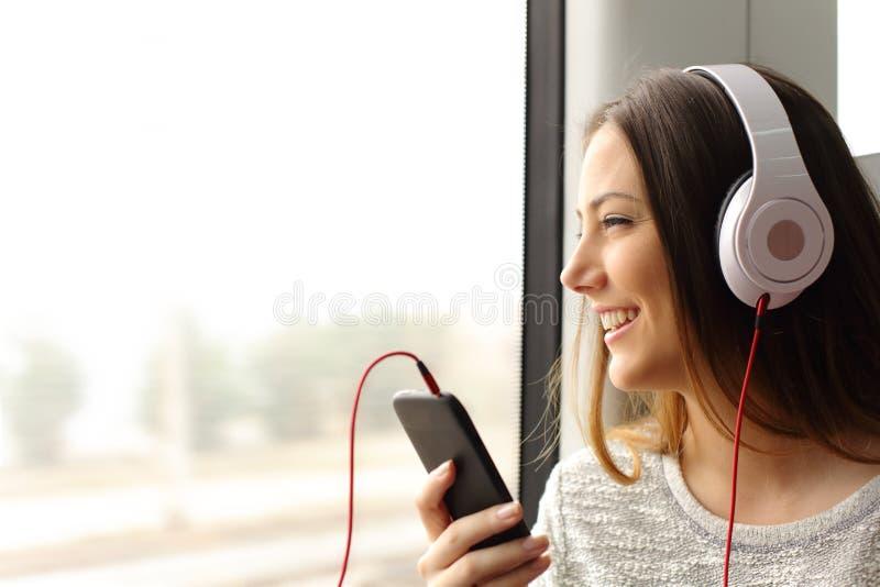 Teen passenger listening to the music traveling in a train. Happy teen passenger listening to the music traveling in a train and looking through the window