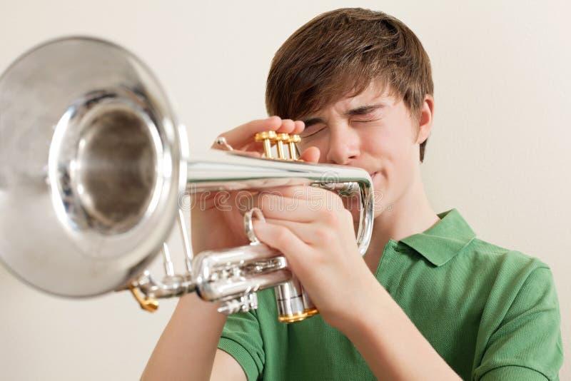 Teen playing silver trumpet stock photos