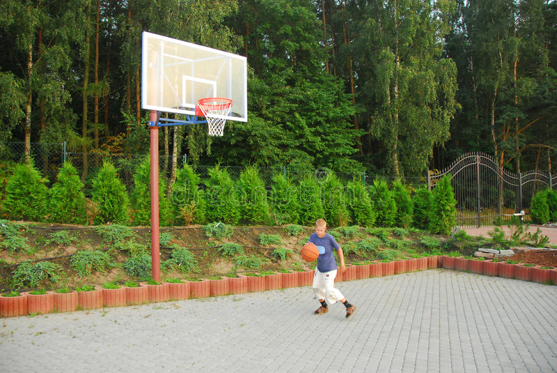 Teen plays basketball royalty free stock photo