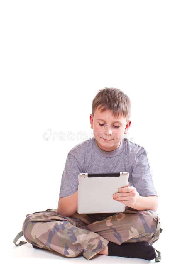Teen plays on the tablet computer stock images