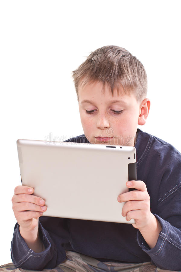 Teen plays on the tablet computer royalty free stock photo