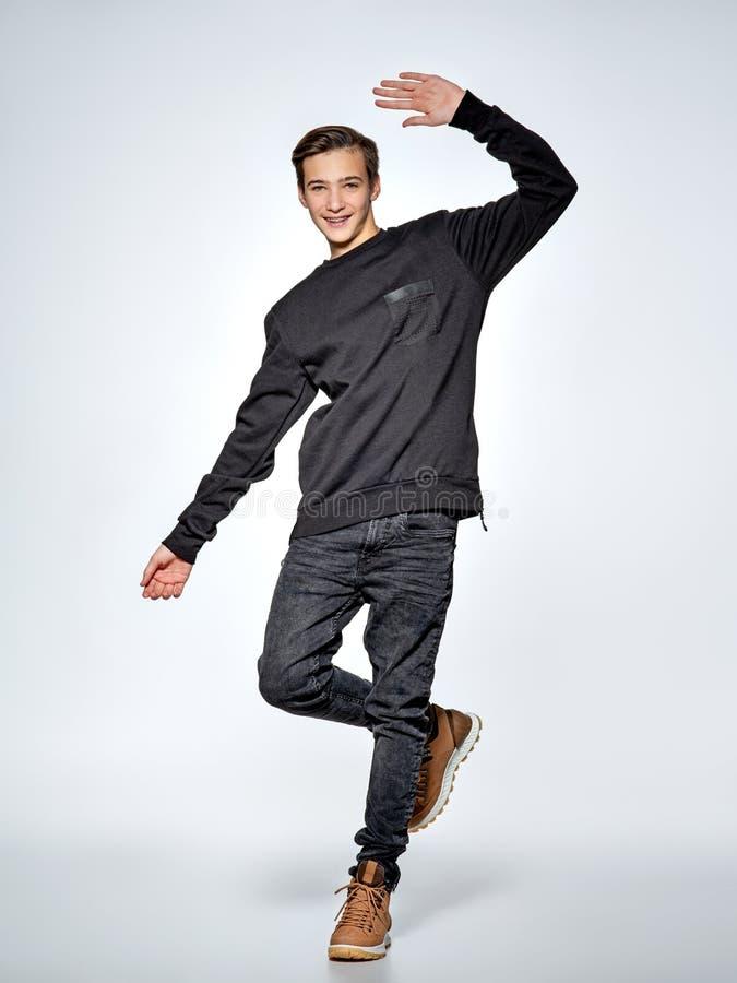 teen pojkedans Iklädd svart moderiktig kläder för tonåring arkivfoto