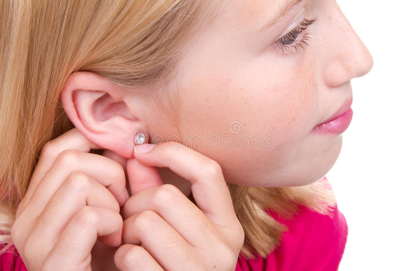 Teen putting in ear ring. Isolated on white royalty free stock images