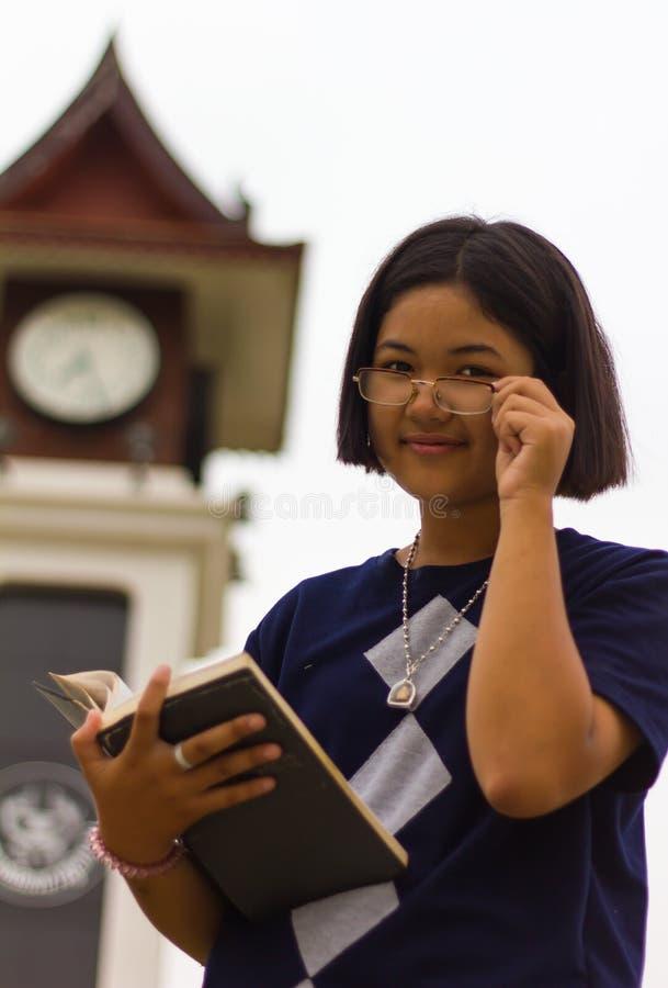 Teen reading clock tower. stock photos