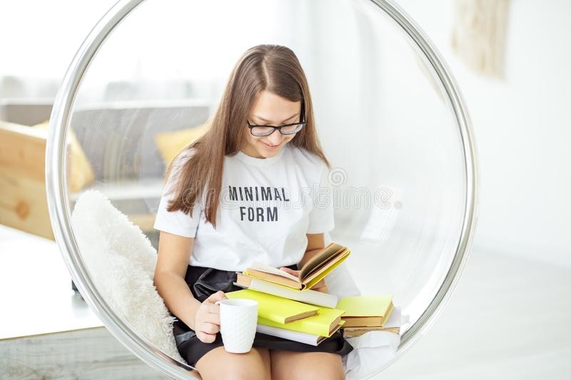 Teen reads an interesting book with glasses. Drinking tea. Concept of education, hobby and study and world book day royalty free stock photo