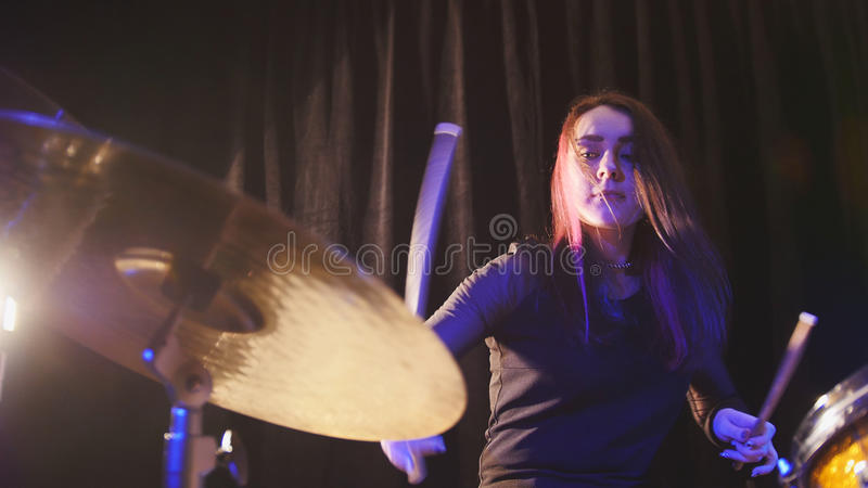 Teen rock music - gothic girl percussion drummer performing with drums stock image