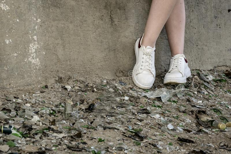 Teen`s feet in a pile of broken glass and debris. troubled Teens and drug addiction stock photo