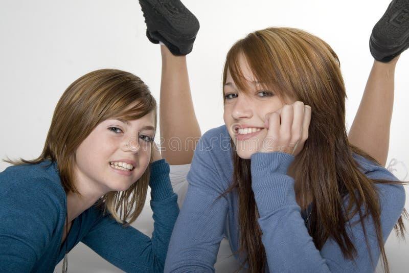 Teen sisters. Two teenage girls lying on floor with feet in air stock image