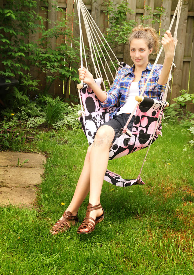 Teen site in a hammock. Blonde teenager sitting in a hammock in a backyard stock photo