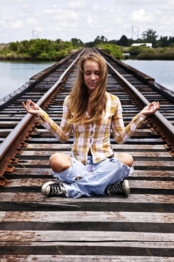 Teen sitting in meditation pose stock photography