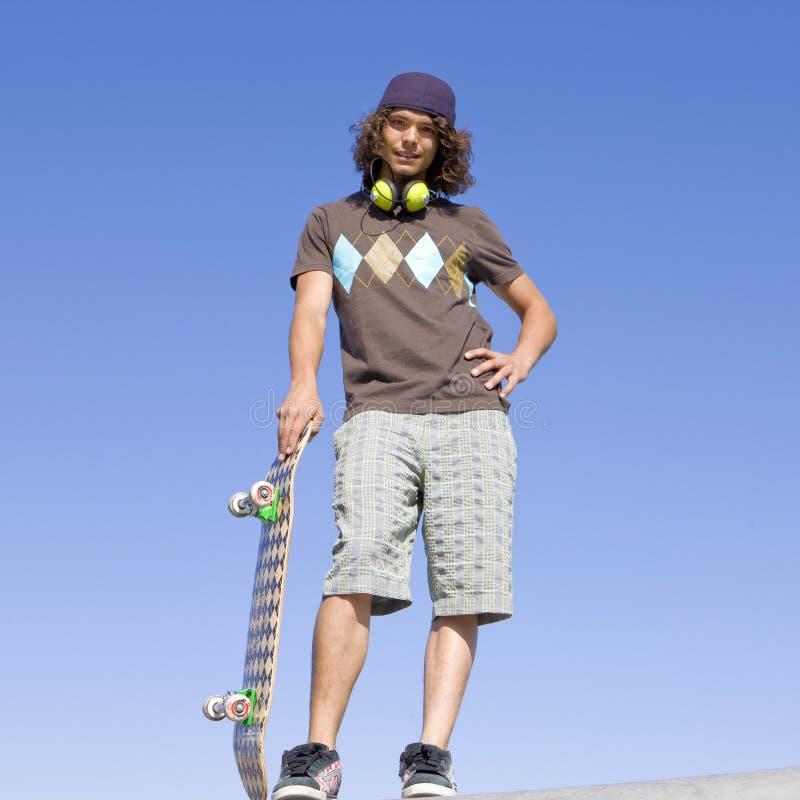 Teen skater atop ramp royalty free stock photo