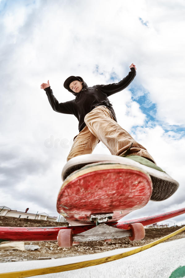 Teen skater in a hoodie sweatshirt and jeans slides over a railing on a skateboard in a skate park royalty free stock photos