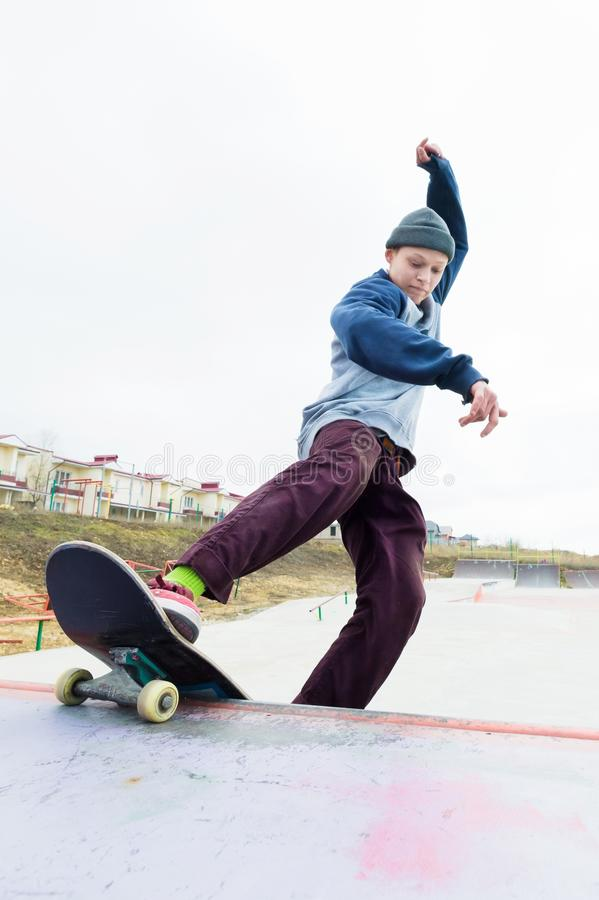 Teen skater in a hoodie sweatshirt and jeans slides over a railing on a skateboard in a skate park royalty free stock photography