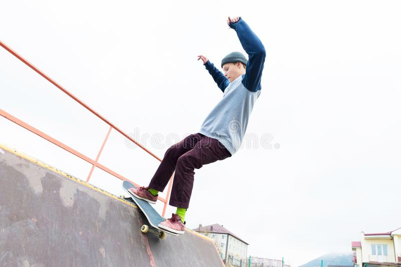 Teen skater in a hoodie sweatshirt and jeans slides over a railing on a skateboard in a skate park royalty free stock photo