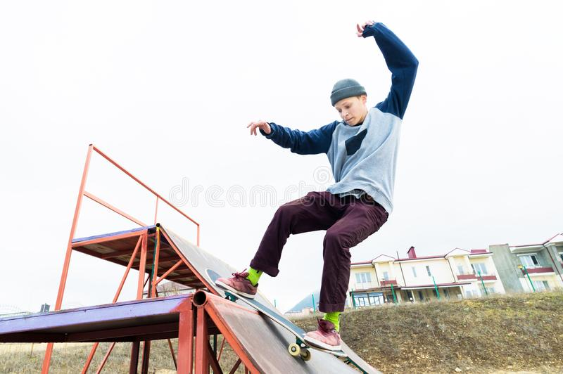 Teen skater in a hoodie sweatshirt and jeans slides over a railing on a skateboard in a skate park stock photo