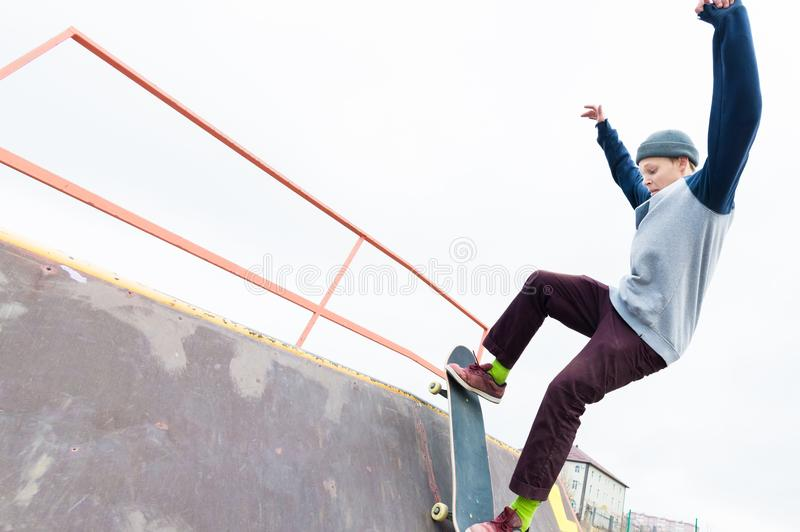 Teen skater in a hoodie sweatshirt and jeans slides over a railing on a skateboard in a skate park stock images