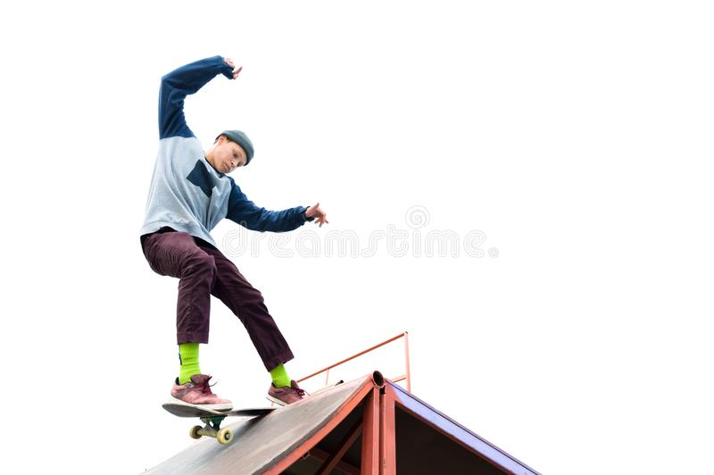 Teen skater in a hoodie sweatshirt and jeans slides over a ramp on a skateboard on white royalty free stock photos