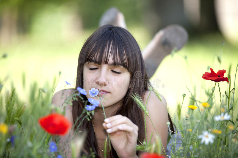 Teen smelling flower. Teen lying in meadow and smelling flowers at springtime stock photos