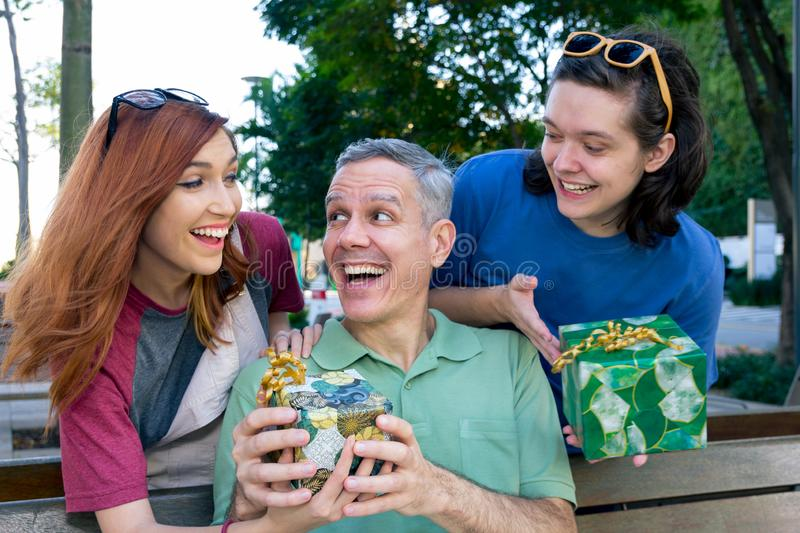 Teen son and daughter surprise dad by giving a present. Fathers Day. Concept of family, relationship, affection stock photos