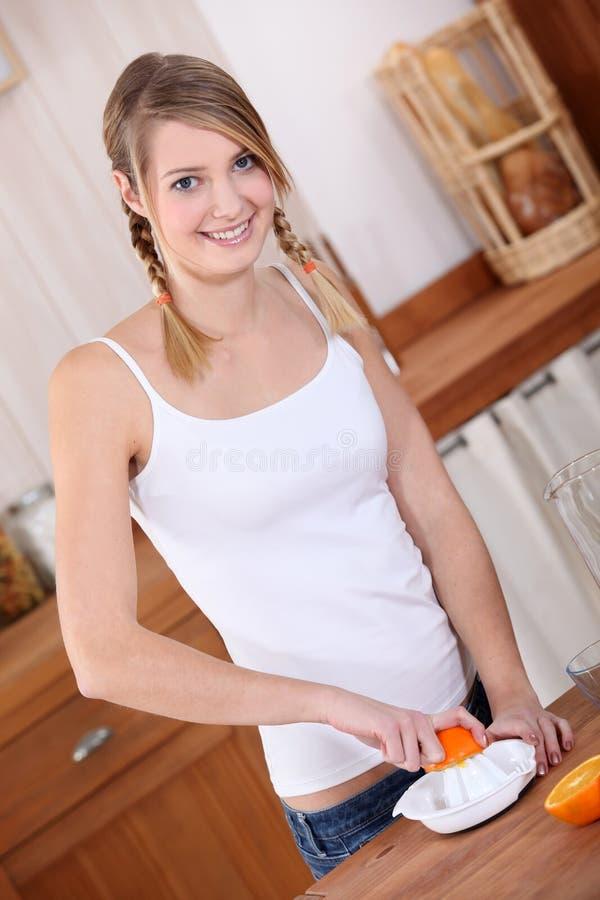 Teen squeezing orange