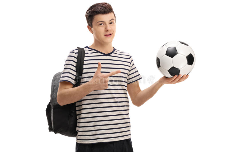 Teen student holding a football and pointing royalty free stock photo